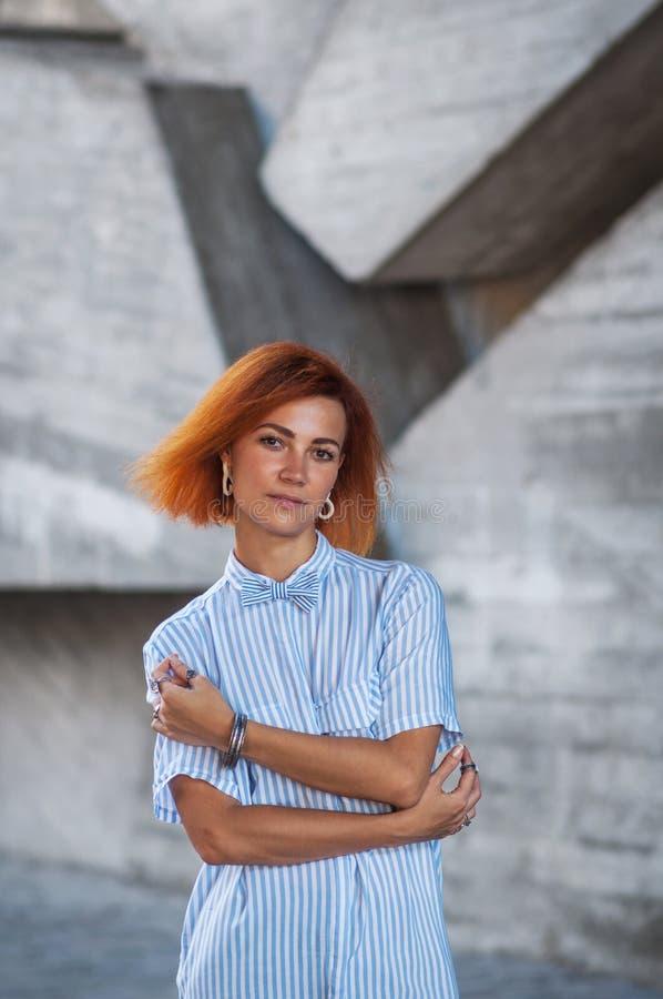 Piękna rudzielec dziewczyna jest ubranym w pasiastej koszula pozuje przeciw tłu betonowa ściana obrazy stock