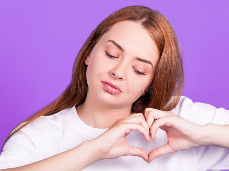 Piękna rudzielec dziewczyna trzyma serce kształtujących palce fotografia royalty free