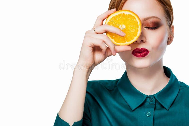 Piękna rudzielec dziewczyna z pomarańcze zdjęcia stock