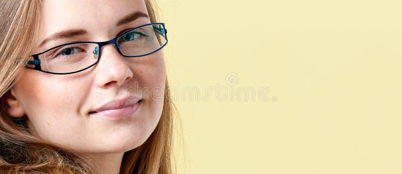 Piękna rudzielec nastolatka dziewczyna jest ubranym czytelniczych szkła z piegami, uśmiechnięty nastoletni portret zdjęcia royalty free