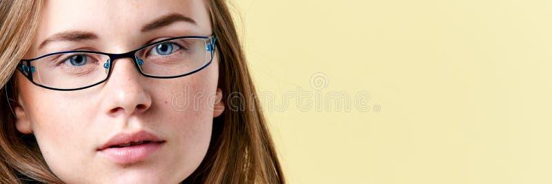 Piękna rudzielec nastolatka dziewczyna jest ubranym czytelniczych szkła z piegami, uśmiechnięty nastoletni portret obraz royalty free