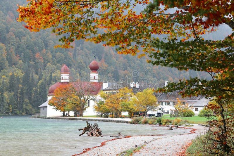 Piękna sceneria Jeziorny Konigssee z sławnym Sankt Bartholomae pielgrzymki kościół jesieni górami w mgłowym i brzeg jeziora obraz stock