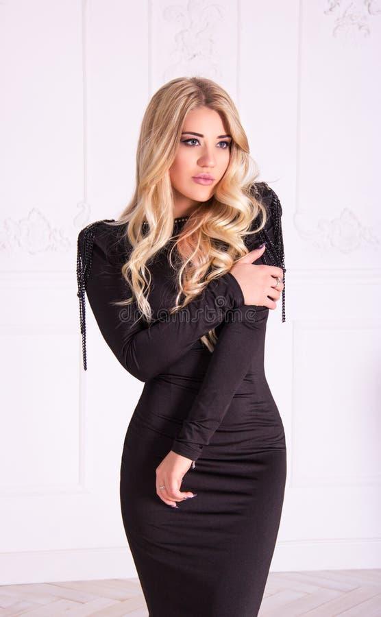 Piękna seksowna blondynka w czerni smokingowy pozować na białym tle obrazy stock