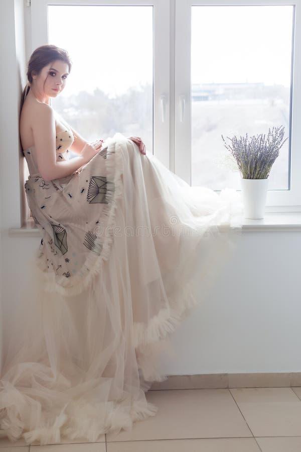 Piękna seksowna brunetki dziewczyna w eleganckiej sukni z długim pociągiem z lawendowymi kwiatami zdjęcie stock