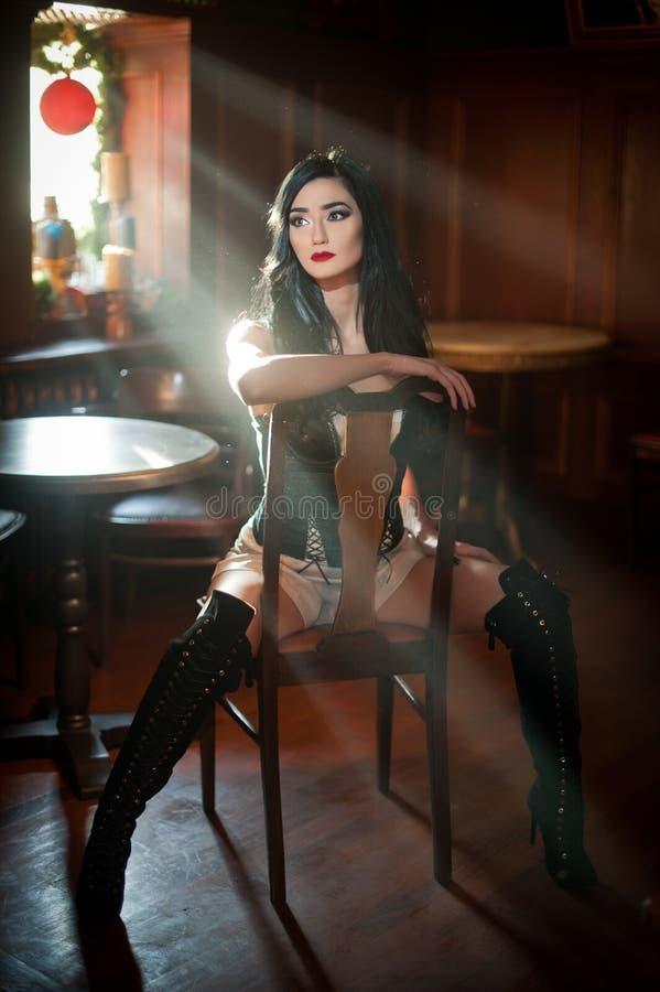 Piękna seksowna dziewczyna siedzi na krześle w wygodnej pozyci z długimi rzemiennymi butami Brunetki kobieta pozuje rzucać wyzwan zdjęcia royalty free
