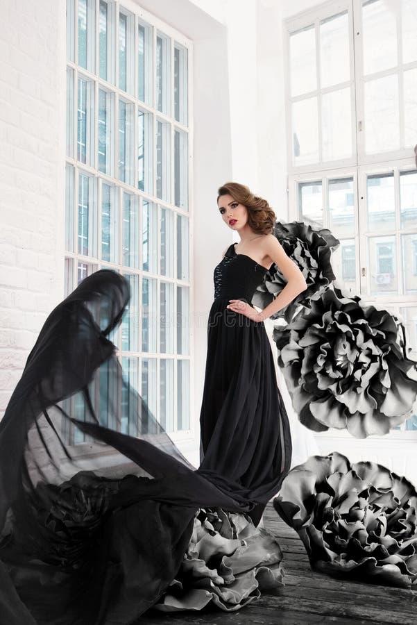 Piękna seksowna dziewczyna w długiej sukni z ogromnym czernią kwitnie zdjęcie royalty free
