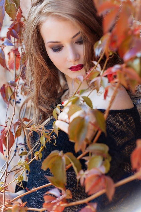 Piękna seksowna elegancka kobieta w czarnej kurtce z jaskrawą czerwoną pomadką na jej wargach z jaskrawym makeup chodzi w parku b fotografia royalty free
