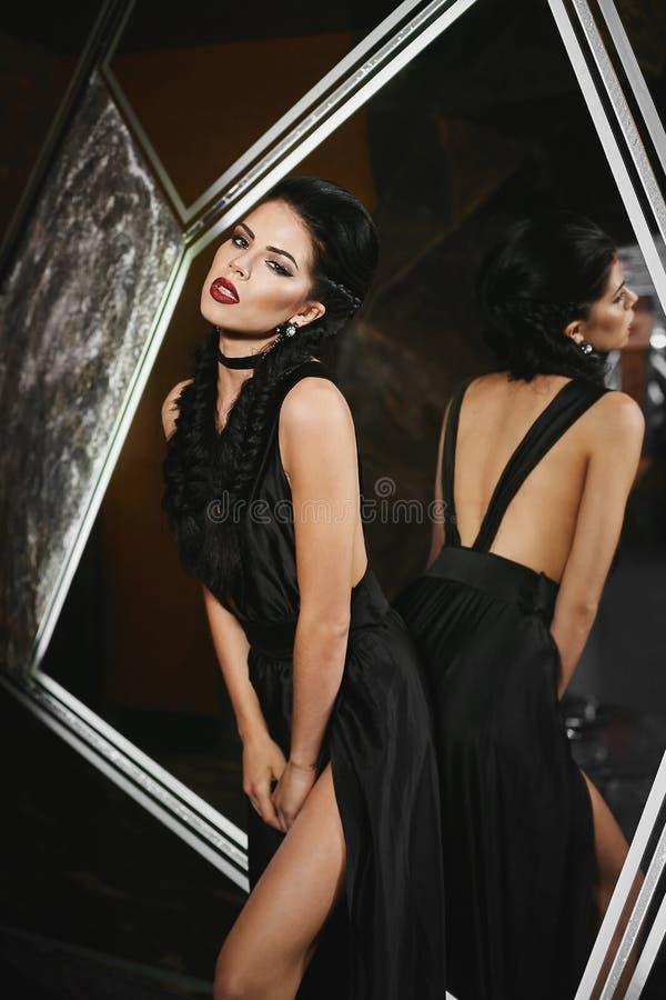 Piękna, seksowna i szczupła brunetka modela dziewczyna w czerni sukni, siedzi w nowożytnym fuzi wnętrzu obrazy royalty free