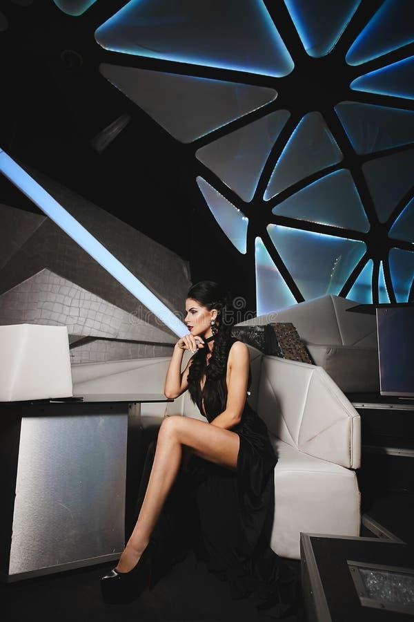Piękna, seksowna i szczupła brunetka modela dziewczyna w czerni sukni, siedzi w nowożytnym fuzi wnętrzu zdjęcie royalty free