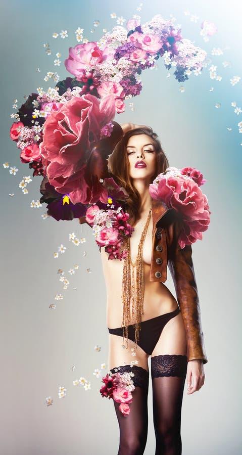 Piękna seksowna kobieta i duzi kwiaty zdjęcia royalty free