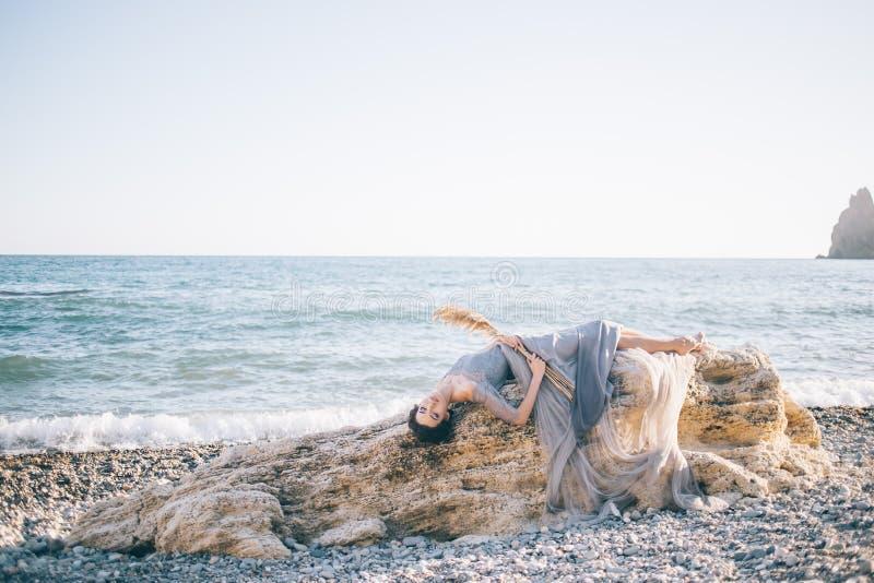Piękna seksowna kobieta w długiej sukni voila kłama na dużym kamieniu blisko morza zdjęcie stock
