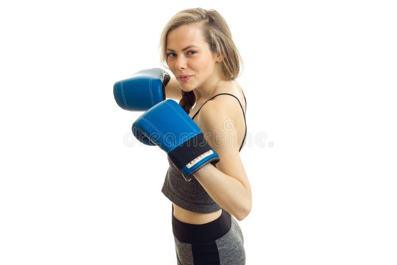 Piękna silna blondynka pozuje przed kamerą w bokserskich rękawiczkach odizolowywa na białym tle zdjęcia royalty free