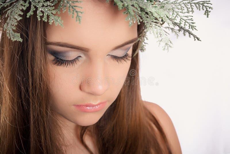 Piękna skromna młoda dziewczyna z jaskrawym makeup, dymiący oczy na nowego roku ` s wianku od choinki i rożki, zdjęcie royalty free
