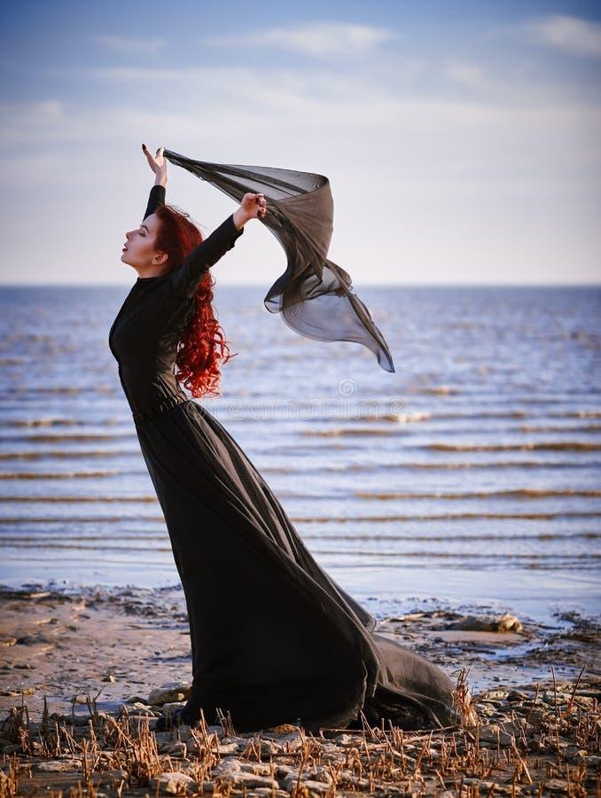 Piękna smutna goth dziewczyna stoi na dennym brzeg z płótnem w rękach zdjęcia stock