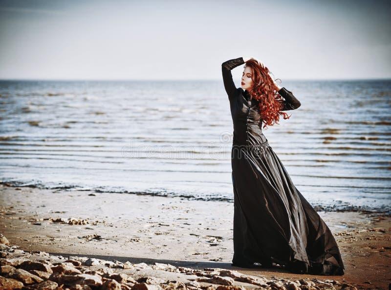 Piękna smutna goth dziewczyny pozycja na morze plaży zdjęcia stock