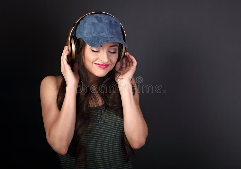 Piękna spokojna młoda kobieta słucha mu w błękitnej baseball nakrętce zdjęcia royalty free