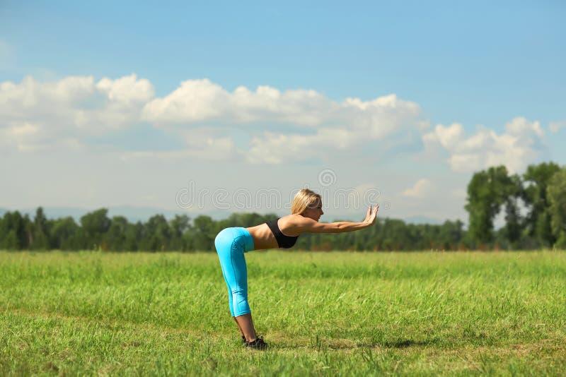 Piękna sport kobieta robi rozciąganie sprawności fizycznej ćwiczeniu w miasto parku przy zieloną trawą zdjęcia royalty free
