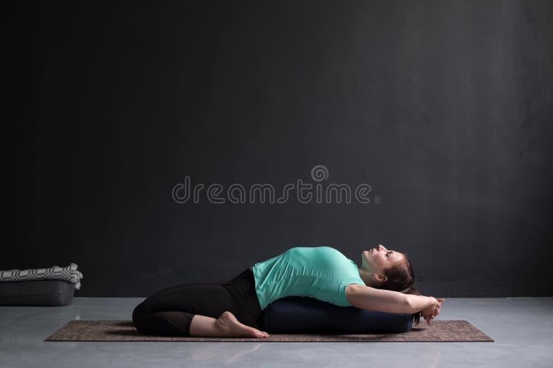Piękna sportowa dziewczyna robi joga supta virasana asana używać podgłówek fotografia royalty free