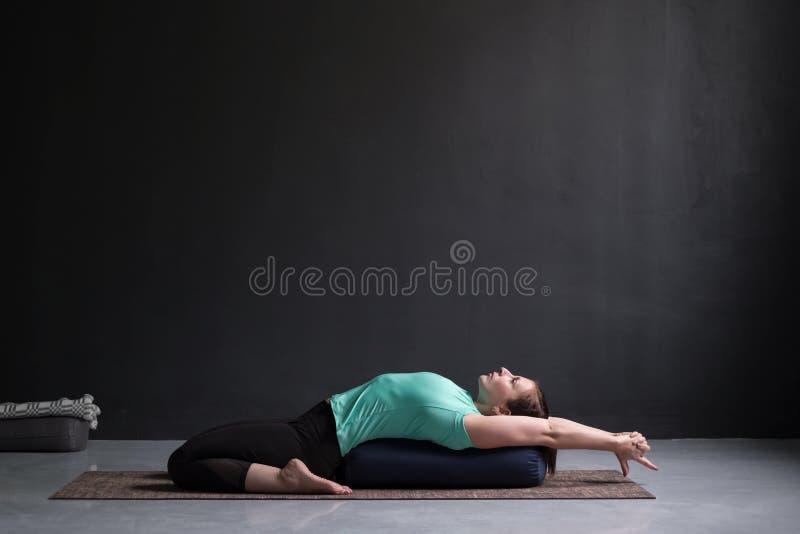 Piękna sportowa dziewczyna robi joga supta virasana asana używać podgłówek obrazy royalty free