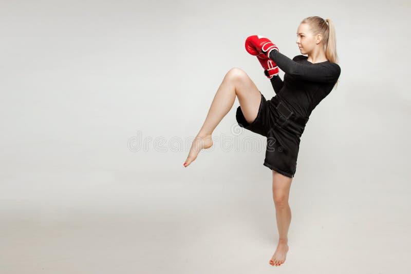 Piękna sportowa dziewczyna z bokserskimi rękawiczkami uderza wysoką stopę obrazy stock