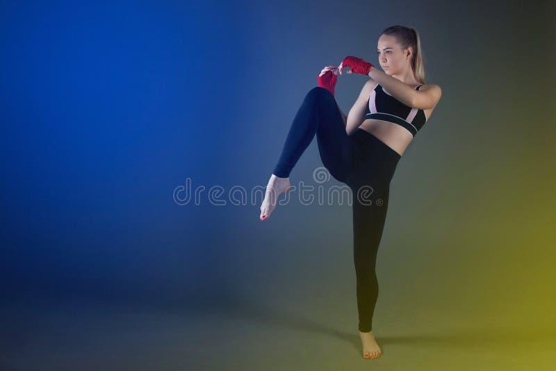 Piękna sportowa dziewczyna z bokserskimi rękawiczkami uderza wysoką stopę obrazy royalty free