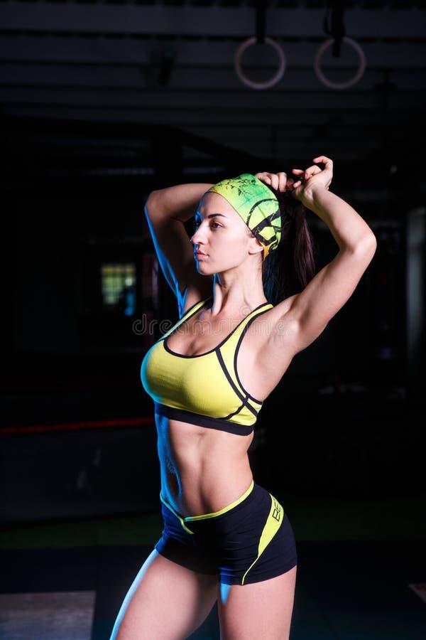 Piękna, sportowa dziewczyny pozycja z rękami podnosić up w gym, Ubierający w skrótach i koszulce z bandażem na jego głowie Spo zdjęcia stock