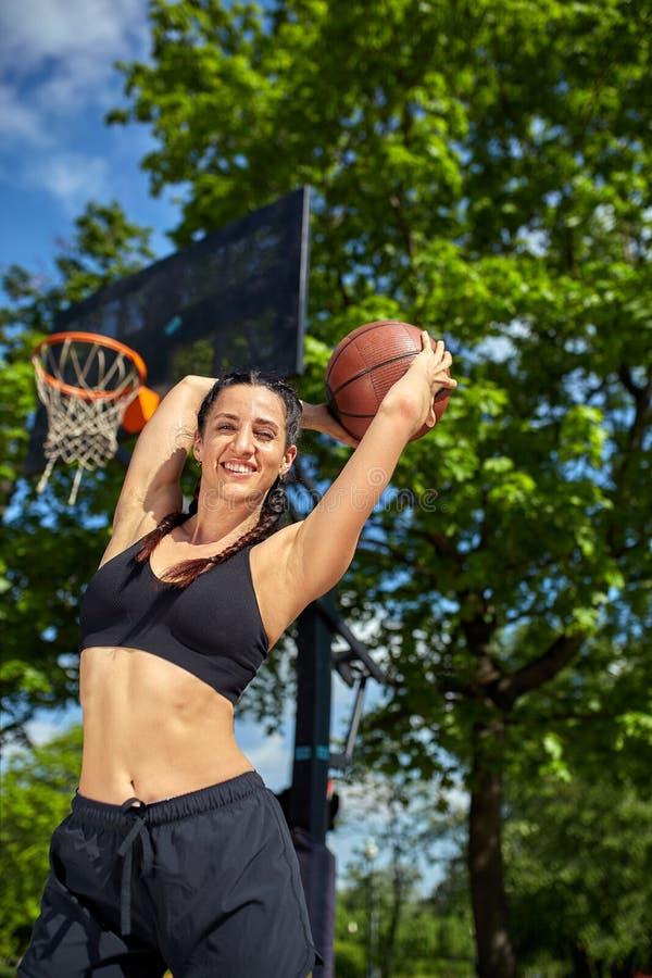 Piękna, sporty łacińska dziewczyna z koszykówką pod pierścionkiem na ulicznym boisku do koszykówki, Sport motywacja, zdrowa fotografia stock