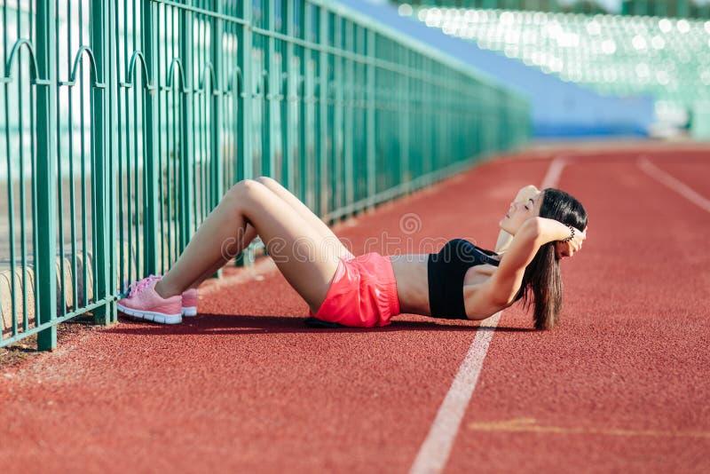 Piękna sporty brunetki kobieta w menchia skrótach i podkoszulek bez rękawów pojawieniu robi ćwiczeniom na żołądku na stadium ślad obrazy stock