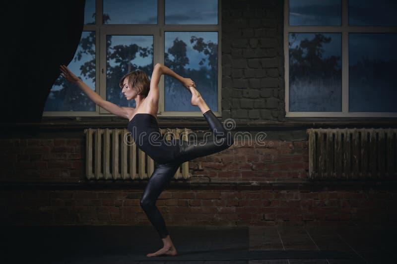 Piękna sporty dysponowana jog kobieta ćwiczy joga asana Natarajasana - władyka taniec poza w ciemnej sala obraz stock