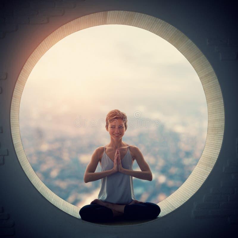 Piękna sporty dysponowana jog kobieta ćwiczy joga asana Padmasana - Lotosowa poza w round okno obraz stock
