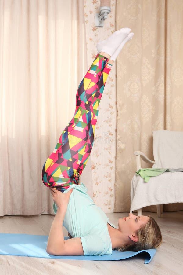 Piękna sporty dysponowana młoda kobieta pracująca out indoors w domu Wzorcowy robi ramię stojaka ćwiczenie, asana Viparita Karany fotografia royalty free