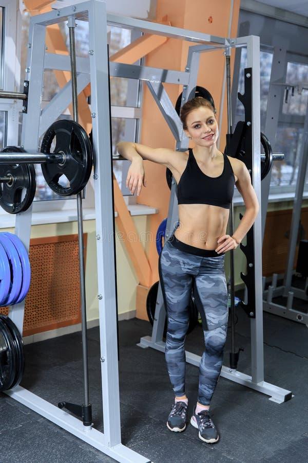 Piękna sporty kobieta uśmiechnięta i odpoczywa nad barbell po mięśniowego szkolenia w sprawności fizycznej centrum obraz royalty free