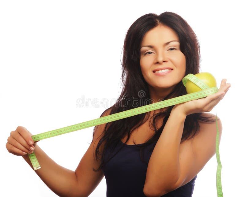 Piękna sporty kobieta z zielonym jabłkiem i pomiarową taśmą zdjęcia royalty free