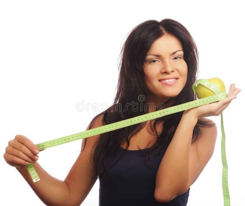Piękna sporty kobieta z zielonym jabłkiem i pomiarową taśmą obrazy royalty free