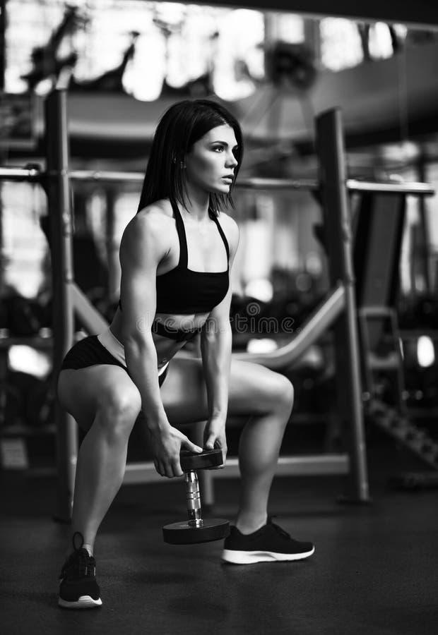 Piękna sporty seksowna kobieta robi pękatemu treningowi w gym zdjęcie stock