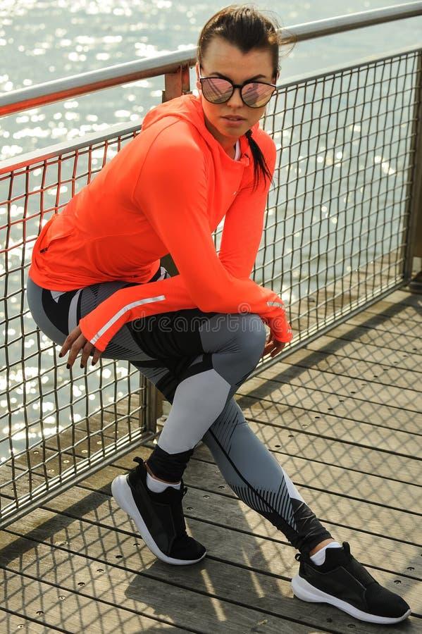 Piękna sprawność fizyczna modela dziewczyna pozuje na molu jest ubranym jaskrawego eleganckiego sportswear fotografia stock
