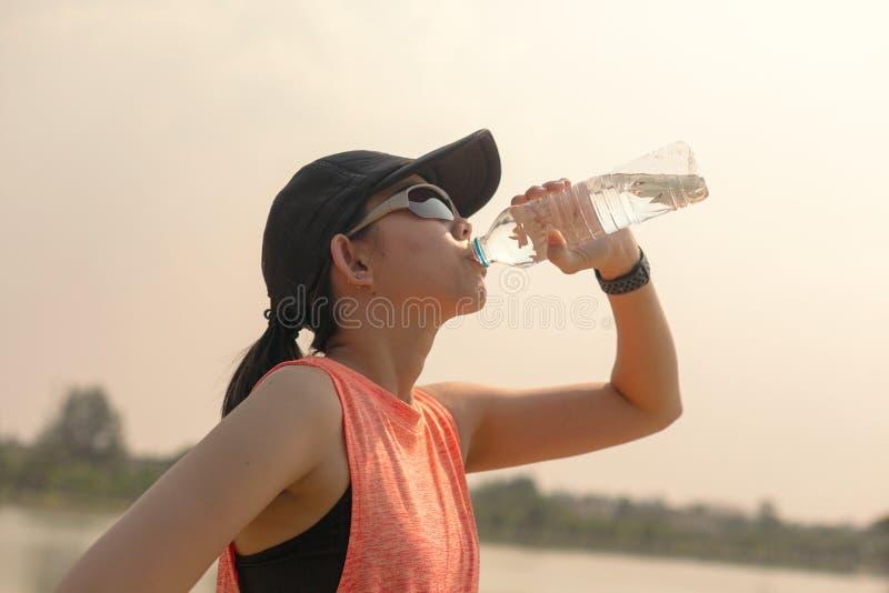 Piękna sprawności fizycznej atlety kobiety woda pitna po opracowywa ćwiczyć dalej Wiecz zdjęcie stock