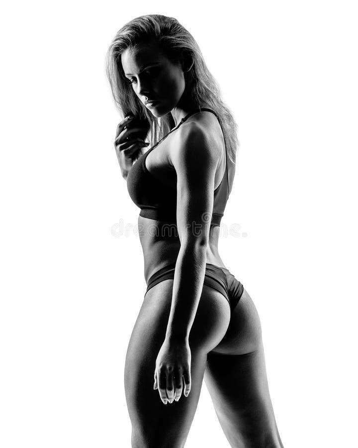 Piękna sprawności fizycznej kobieta pozuje na pracownianym tle fotografia stock