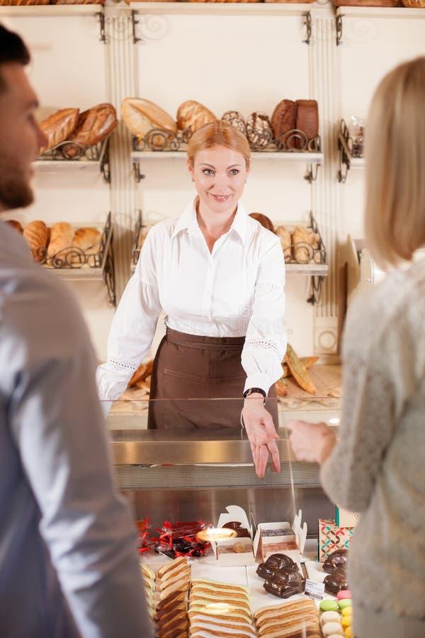 Piękna sprzedawczyni sprzedaje piekarnia produkty obrazy royalty free