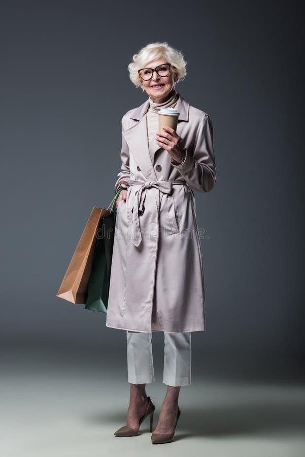 piękna starsza dama w okopu żakieta mienia torba na zakupy i kawie iść, fotografia royalty free
