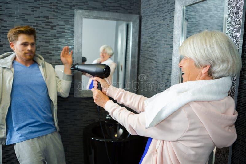 Piękna starsza kobieta ma zabawę z włosianą suszarką obrazy stock
