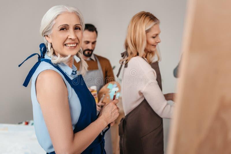 piękna starsza kobieta ono uśmiecha się przy kamerą podczas sztuki klasy zdjęcia stock