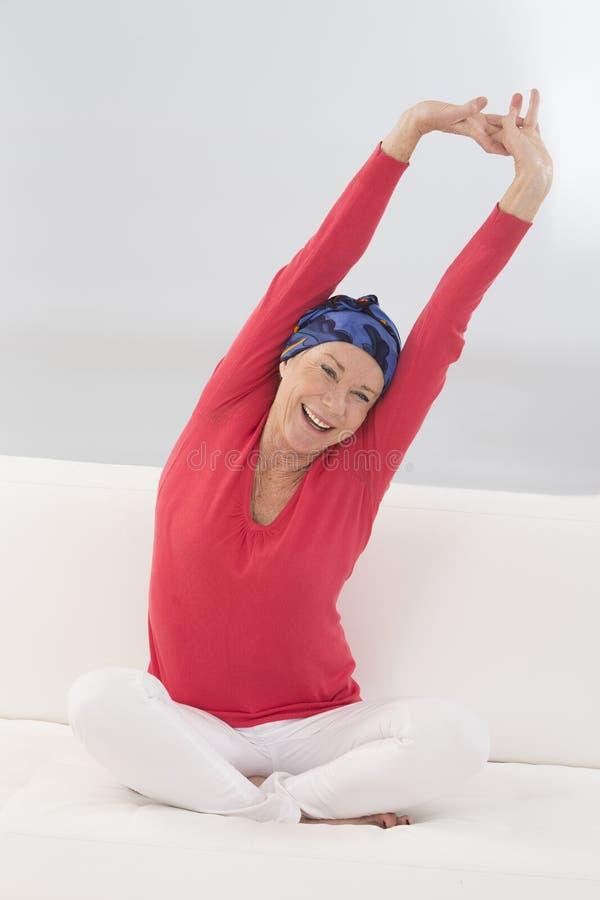 Piękna starsza kobieta relaksuje w domu w jej łóżkowej ręce i s up zdjęcie royalty free