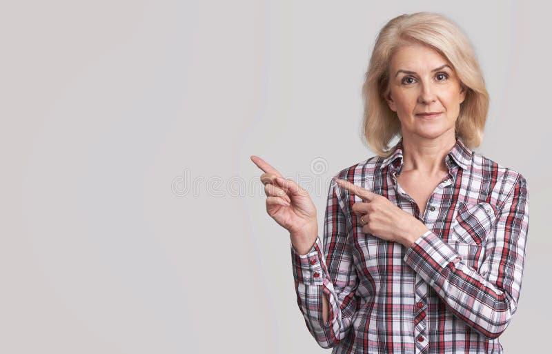 Piękna starsza kobieta wskazuje kopiować przestrzeń fotografia royalty free