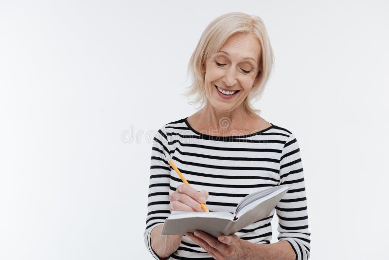 Piękna starzejąca się kobieta robi notatkom fotografia stock