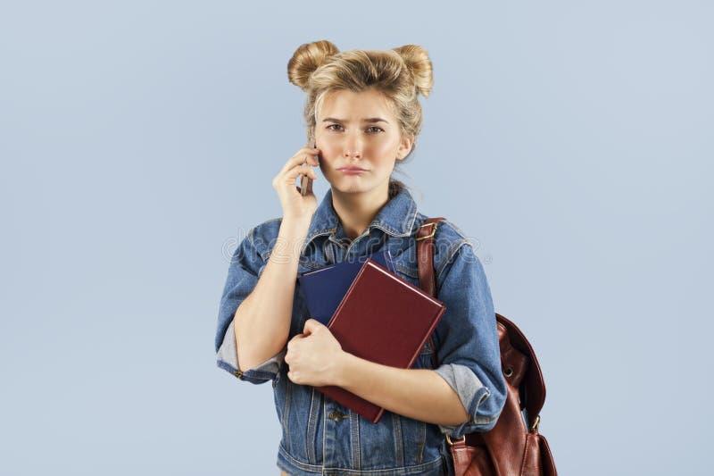 Piękna studencka dziewczyna w drelichowej kurtce z plecakiem na ona ramiona w studiu na błękitnym tle Pojęcie obraz royalty free