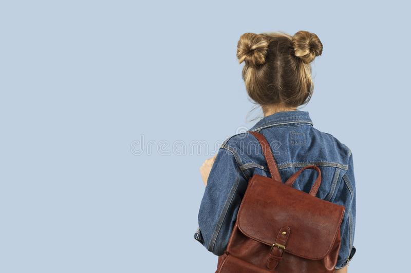 Piękna studencka dziewczyna w drelichowej kurtce z plecakiem na ona ramiona w studiu na błękitnym tle Pojęcie zdjęcie stock