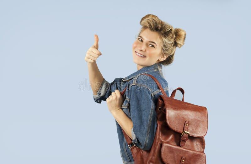 Piękna studencka dziewczyna w drelichowej kurtce z plecakiem na ona ramiona w studiu na błękitnym tle Pojęcie obrazy stock
