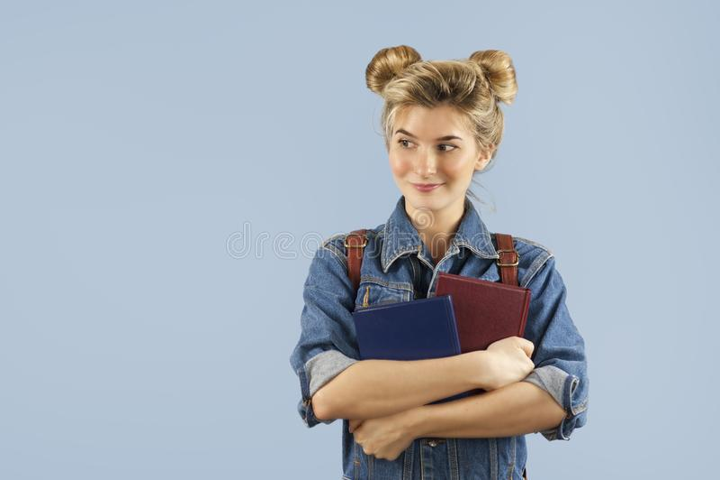 Piękna studencka dziewczyna w drelichowej kurtce z plecakiem na ona ramiona w studiu na błękitnym tle Pojęcie zdjęcia royalty free