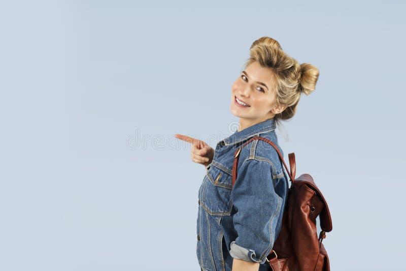 Piękna studencka dziewczyna w drelichowej kurtce z plecakiem na ona ramiona w studiu na błękitnym tle Pojęcie obrazy royalty free
